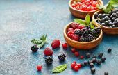 Various summer fruits in a wooden bowls. Assorted fresh berries with leaves on metal background.  poster