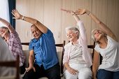 Senior people stretching while sitting on chairs at retirement home poster