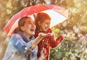 Happy funny family with red umbrella under the autumn shower. Girl and her mother are enjoying rainf poster