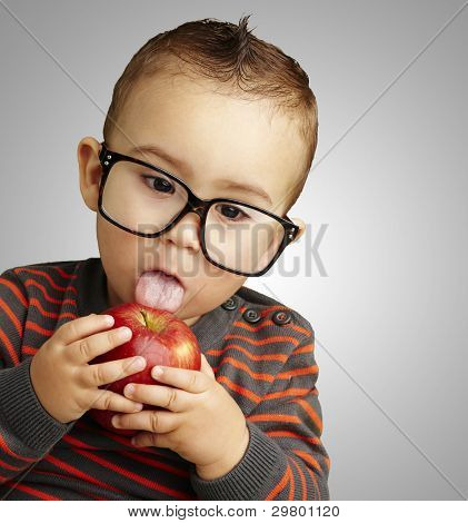 portrait of a handsome kid wearing glasses licking a red apple over a grey background