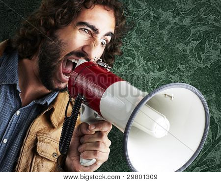 portrait of young man shouting with megaphone against a vintage wall