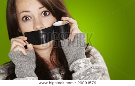 portrait of scared girl being silenced by herself over green background