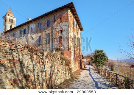 Old abbandoned brick house and church's belfry in town of La Morra, Northern Italy.