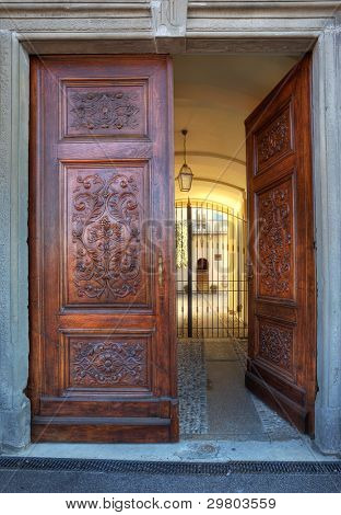 Vertical oriented image of beautiful ornate wooden door at the entrance to small courtyard in town of La Morra, Northern Italy.