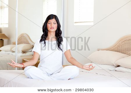 beautiful young woman practicing yoga meditation on her bed