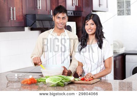 young indian couple cooking in kitchen