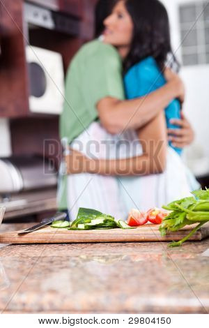 young couple hugging in kitchen, focus on foreground