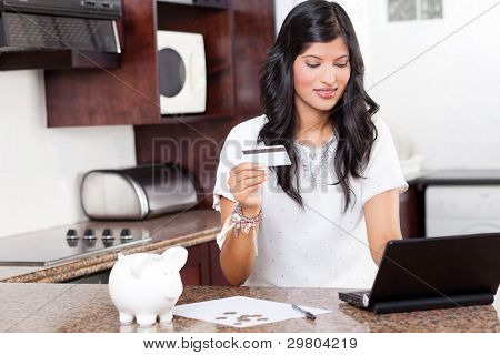 beautiful young indian woman using credit card shopping online