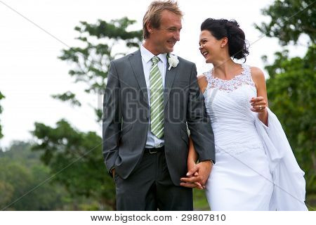 Bride And Groom Walking Holding Hands In A  Rural Setting