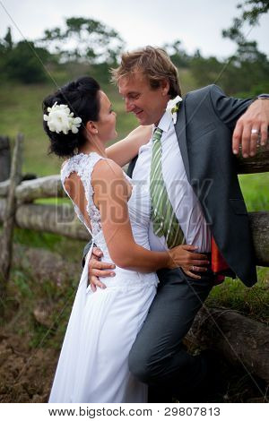 Bride And Groom Embracing Against A Fence