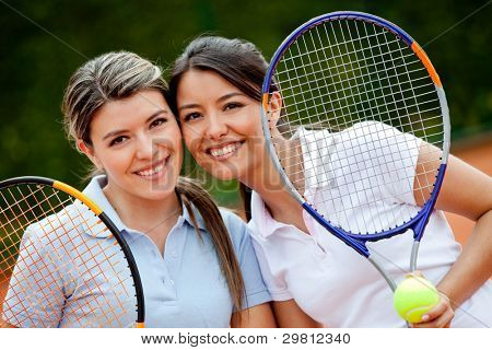Beautiful female tennis players holding rackets and smiling