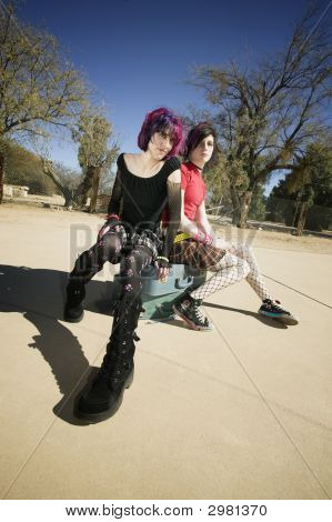 Two Punk Girls Sitting On Suitcases