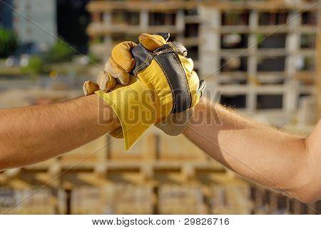 Handshake over building site