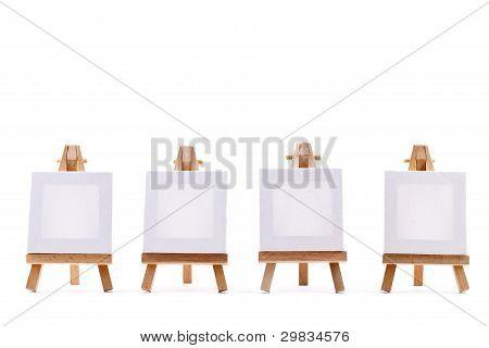 Quatro telas em branco sobre cavaletes