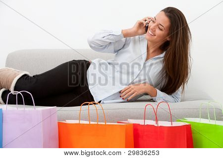 Girl On Couch With Mobile And Shopping Bags