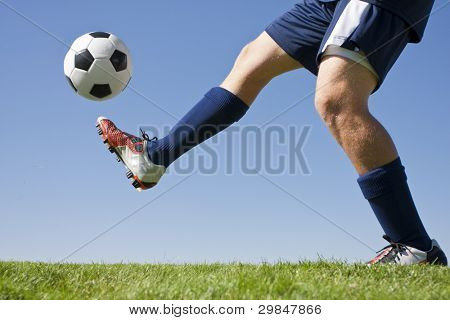 Athlete Kicking a soccer ball on field