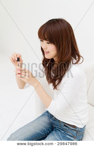 Beautiful asian woman painting her nails