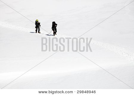 Team of alpinists traversing a glacier