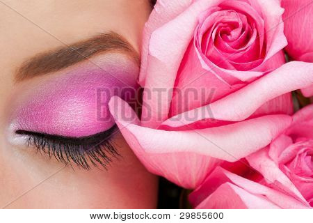 Close-up of closed woman eye with bright stylish makeup and pink roses