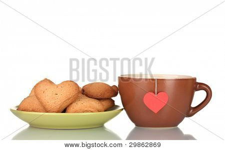 Brown cup with tea bag and heart-shaped cookies on green plate isolated on white