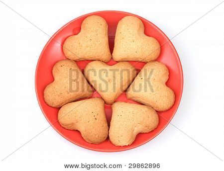 Heart-shaped cookies on red saucer isolated on white