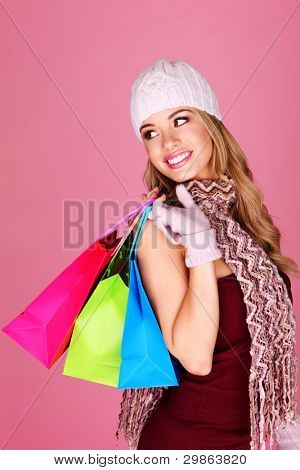 Beautiful Blonde Shopping. Beautiful blonde woman in winter accessories carrying colorful shopping bags looking back over her shoulder