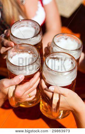 Cuatro amigos con una cerveza fresca en un jardín, cerca de cerveza en stein cerveza