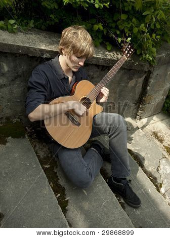 Young man sitting on old cement stairway, playing a classical guitar.