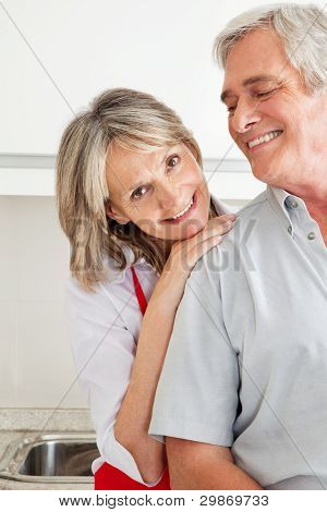 Senior woman in kitchen leaning on shoulder of man