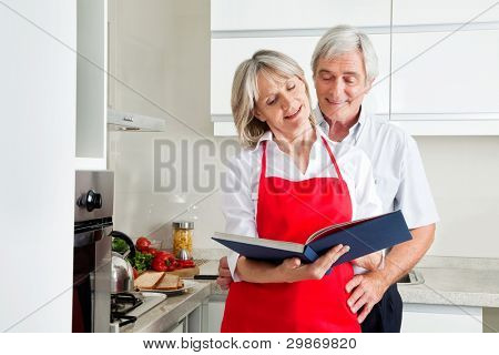 Happy senior couple in kitching looking for recipes in a cookbook