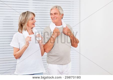 Happy senior couple exercising in fitness center