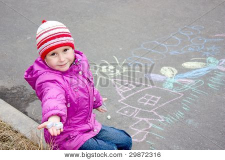 Girl drawing on the asphalt.