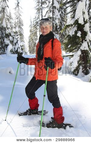 Seventy year old lady having fun snowshoeing on Mount Seymour, Vancouver, Canada.
