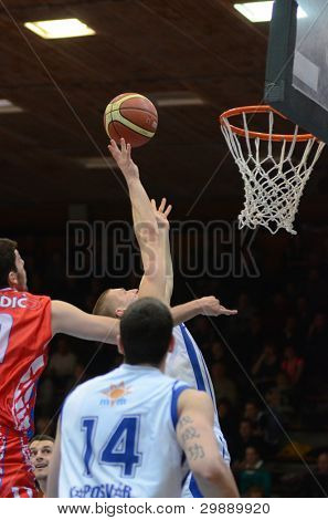 KAPOSVAR, HUNGARY - JANUARY 28: Nik Raivio (with ball) in action at a Hungarian Championship basketball game with Kaposvar (white) vs. Nyiregyhaza (red) on January 28, 2012 in Kaposvar, Hungary.