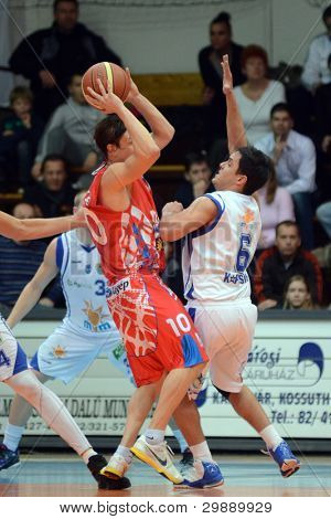 KAPOSVAR, HUNGARY - JANUARY 28: Kornel Kiss (in white) in action at a Hungarian Championship basketball game with Kaposvar (white) vs. Nyiregyhaza (red) on January 28, 2012 in Kaposvar, Hungary.