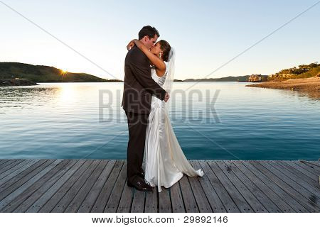 Newlyweds Kissing On A Jetty At Sunset