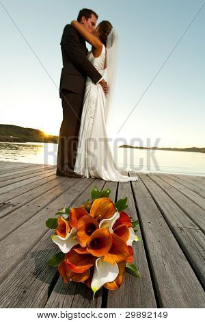 Wedding Bouquet In Foreground And Newlyweds Kissing Behind