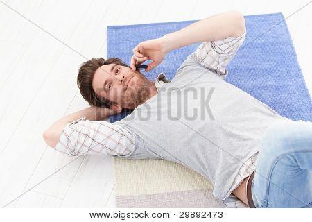 schöner junge Mann Handauflegen Boden im Wohnzimmer, im Chat auf Handy, lächelnd.?