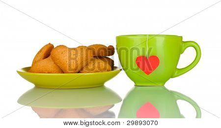 Green cup with tea bag and heart-shaped cookies on green plate isolated on white