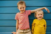 Outdoor Summer Portrait Of Two Cute Happy Playful Kids, Big Brother And His Little Sister Against Bl poster