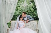 Wedding. The Bride And Groom Are Sitting On A Beautiful Couch In A Gazebo In The Garden. The Bride I poster