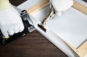 Canvas Stretching. Wooden Stretcher Bar, Staple Gun, Canvas Pliers, Male Hand In White Protect Glove poster