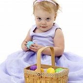 pic of easter basket eggs  - Little girl in a purple dress sits holding a blue egg with an Easter basket full of colorful eggs in front of her.