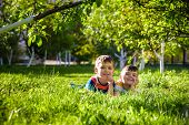 Happy Children Having Fun Outdoors. Kids Playing In Summer Park. Little Boy And His Brother Laying O poster