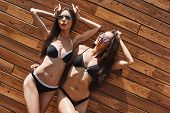 Playful Beauty. Carefree Cute And Young Women In Swimwear And Sunglasses Are Having Fun And Enjoying poster