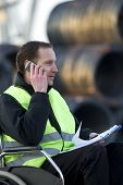 stock photo of physically handicapped  - Physically challenged supervisor on call with notepad at industrial site - JPG