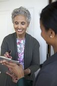 picture of soliciting  - Black senior woman signs a petition at her front door - JPG