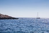 Island Stone Shore And Sailing Boat Sail On A Blue Sea In A Bright Sunny Summer Season poster