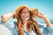 Closeup face of mature woman wearing straw hat enjoying the sun at beach. Happy woman smiling during poster