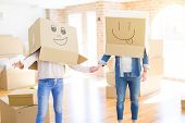 Couple having fun at new apartment wearing boxes with funny faces over head poster
